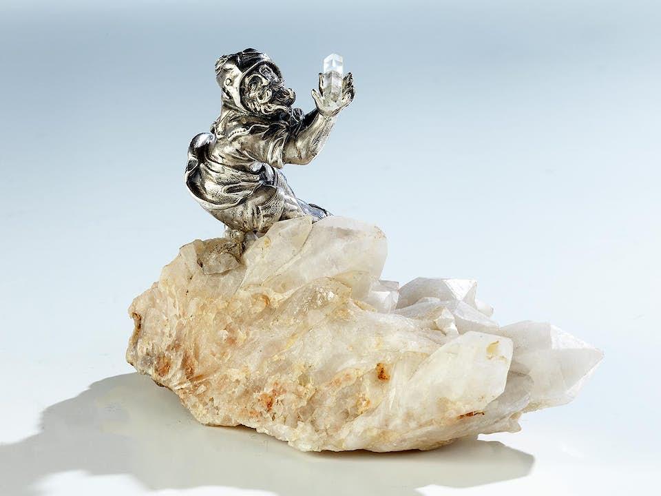 Schatzsuchender silberner Bergwicht auf Bergkristallstufe